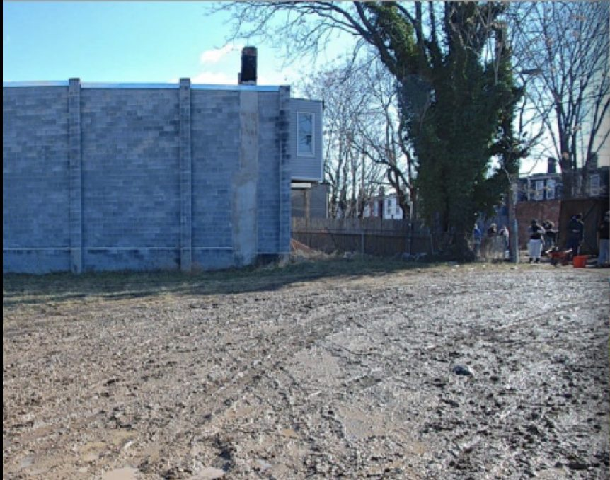 Darley Park Before image, big empty muddy space in front a plain stone wall.